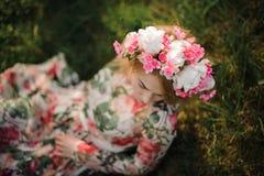 Junges Mädchen in einem Blumendiadem, das auf dem Gras sitzt Stockbilder