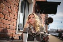 Junges Mädchen an einem Cafétisch Lizenzfreie Stockfotos