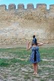 Junges Mädchen in einem Kleid mit einem Sturzhelm auf ihrem Kopf nahe der Festungswand lizenzfreie stockfotografie
