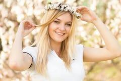 Junges Mädchen in einem Kranz von Blumen mit Aprikose Lizenzfreie Stockfotos