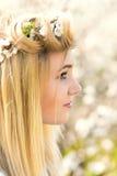 Junges Mädchen in einem Kranz von Blumen mit Aprikose Stockfoto