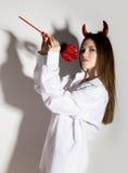 Junges Mädchen in einem Mann ` s weißen Hemd mit den roten Hörnern, die Dreizack und Aussehung wie hübscher Teufel halten Lizenzfreies Stockbild