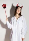 Junges Mädchen in einem Mann ` s weißen Hemd mit den roten Hörnern, die Dreizack und Aussehung wie hübscher Teufel halten Stockfotografie