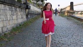 Junges Mädchen in einem roten Kleid geht, entlang Pflasterungsstadtufergegend fröhlich zu überspringen stock video