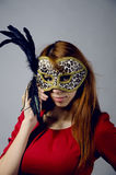 Junges Mädchen in einem roten Kleid und in einer Maske Lizenzfreie Stockfotos