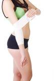 Junges Mädchen in einem Sportträgershirt und -kurzen Hosen verbindet seinen Arm mit einer elastischen Binde Lizenzfreies Stockbild