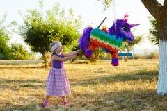 Junges Mädchen an einer Partei im Freien, die einen Pinata schlägt lizenzfreies stockfoto