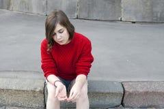 Junges Mädchen in einer roten der Wollstrickjacke und -kurzen Jeanshose sitzt auf den Schritten stockfotografie