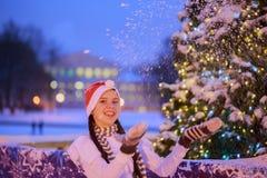 Junges Mädchen in einer roten Kappe steht nahe einem Weihnachtsbaum Sie wirft Stockbild
