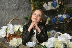 Junges Mädchen in einer schwarzen Lederjacke mit Blumen lizenzfreie stockfotos