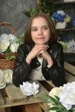 Junges Mädchen in einer schwarzen Lederjacke mit Blumen lizenzfreie stockbilder
