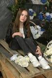 Junges Mädchen in einer schwarzen Lederjacke mit Blumen lizenzfreies stockfoto