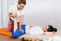 Junges Mädchen erhalten thailändische Artmassage durch Frau für Körpertherapie lizenzfreie stockfotos