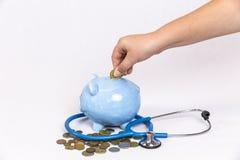 Junges Mädchen-fallende Goldmünze in blaues Sparschwein Lizenzfreie Stockfotografie