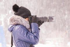 Junges Mädchen fotografierte im Winter in einem Schneesturm auf einer SLR-Kamera mit Teleobjektiv Lizenzfreie Stockfotos