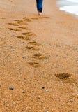Junges Mädchen geht hinunter den Strand, der Bahn im Sand lässt Stockbild