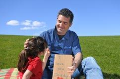 Junges Mädchen gibt ihre Vaterblume und eine Karte stockfotos