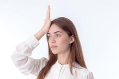 Junges Mädchen hält Hand hinter seinem Kopf und blickt in Richtung lokalisiert auf weißem Hintergrund Stockbild