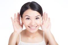 Junges Mädchen hören durch Ohr mit Lächeln lizenzfreie stockfotografie