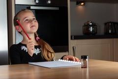 Junges Mädchen hat die Lösung beim Handeln von Hausarbeit am Küchentisch gefunden, der einen Bleistift hochhält Stockbild