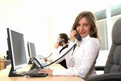 Junges Mädchen im Büro auf dem Arbeitsplatz bildet Aufruf Stockbilder