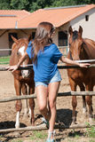 Junges Mädchen im Bauernhof umgeben durch Pferde Lizenzfreie Stockbilder