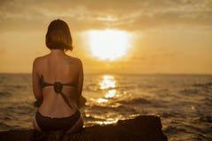 Junges Mädchen im Bikini, der auf einem Felsen auf einer Küste sitzt lizenzfreie stockbilder