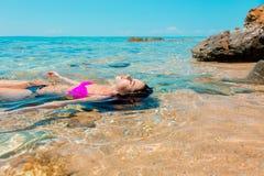 Junges Mädchen im Bikini, der sich in einem Wasser hinlegt lizenzfreie stockfotografie