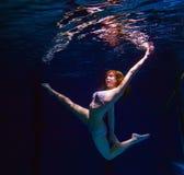 Junges Mädchen im Bikini, der unter Wasser aufwirft Lizenzfreie Stockfotografie