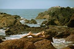 Junges Mädchen im Bikini mit schönem Körper und in der Sonnenbrille, die auf den Steinen auf dem Strand liegt Lizenzfreie Stockfotografie