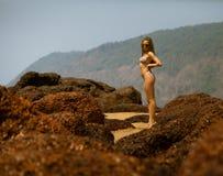 Junges Mädchen im Bikini mit schönem Körper und in der Sonnenbrille nahe roten Steinen auf dem Strand Lizenzfreie Stockbilder
