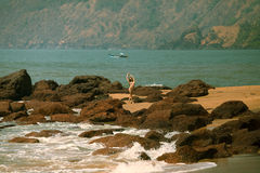 Junges Mädchen im Bikini mit schönem Körper und in der Sonnenbrille nahe roten Steinen auf dem Strand Lizenzfreies Stockfoto
