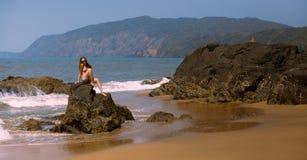 Junges Mädchen im Bikini und in Sonnenbrille, die auf den Steinen auf dem Strand sitzen Lizenzfreie Stockfotos