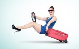 Junges Mädchen im blauen Kleid und in der Sonnenbrille mit Lenkrad geht auf eine Kreuzfahrt Reise durch Autokonzept Stockbild