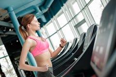 Junges Mädchen im gesunden Lebensstil der Turnhalle, der auf der Tretmühle heraus schaut das Fenster aufgeregt läuft stockbild