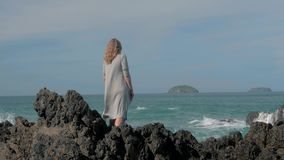Junges Mädchen im grauen Kap, das nahe den Sturmwellen schlagen das junge Mädchen der Felsen heraus schaut zum Ozean, Wellenbrech stock video