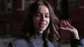Junges Mädchen im grauen Mantel, untersucht Kamera, geraderichtet ihr Haarlächeln Abschluss oben stock video