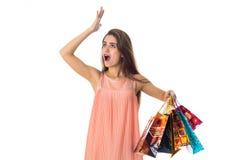 Junges Mädchen im hellen Kleid blickt in Richtung des angehobenen Armes oben, während die andere Hand Los Pakete wird lokalisiert Stockfotografie