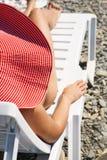 Junges Mädchen im Hut, der auf Aufenthaltsraum sitzt stockfoto