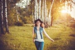 Junges Mädchen im Park mit Blumen lizenzfreies stockfoto