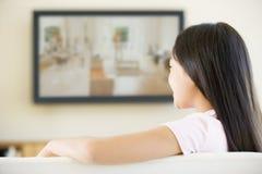 Junges Mädchen im Raum mit Fernsehen des flachen Bildschirms Lizenzfreies Stockbild