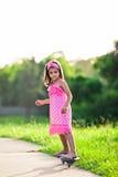 Junges Mädchen im rosafarbenen Kleidreiten auf Skateboard lizenzfreie stockfotografie