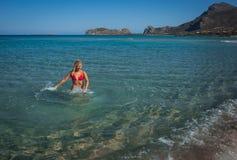 Junges Mädchen im roten Bikini, der mit Meerwasser spielt Lizenzfreie Stockfotos