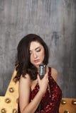 Junges Mädchen im roten Cocktailkleid singend mit Mikrofon Lizenzfreies Stockbild