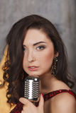 Junges Mädchen im roten Cocktailkleid singend mit Mikrofon Lizenzfreies Stockfoto