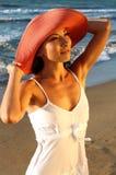 Junges Mädchen im roten Hut auf dem Strand Stockfotos