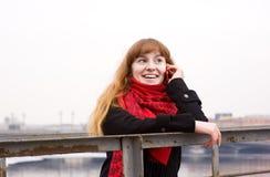 Junges Mädchen im roten Schal um Telefon ersuchend Stockfotografie