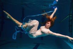 Junges Mädchen im schönen weißen Kleid, das unter Wasser aufwirft Stockbild