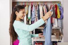 Junges Mädchen im Schlafzimmer, das Kleidung vom Wandschrank wählt stockfotografie