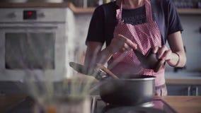 Junges Mädchen im Schutzblech, das Lebensmittel in der Küche zubereitet stock footage